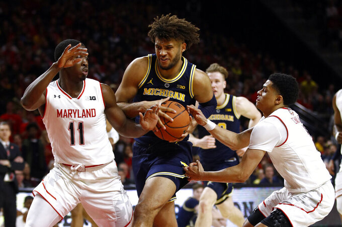 Michigan forward Isaiah Livers, center, drives between Maryland guards Darryl Morsell, left, and Anthony Cowan Jr. in the first half of an NCAA college basketball game, Sunday, March 3, 2019, in College Park, Md. (AP Photo/Patrick Semansky)