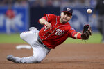 Washington Nationals second baseman Brian Dozier flips the ball to first base late on a single by San Diego Padres' Manny Machado during the third inning of a baseball game Saturday, June 8, 2019, in San Diego. (AP Photo/Orlando Ramirez)