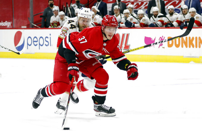 Carolina Hurricanes' Andrei Svechnikov (37) brings the puck up the ice after taking it away from Florida Panthers' Kevin Connauton (44) during the second period of an NHL hockey game in Raleigh, N.C., Sunday, March 7, 2021. (AP Photo/Karl B DeBlaker)