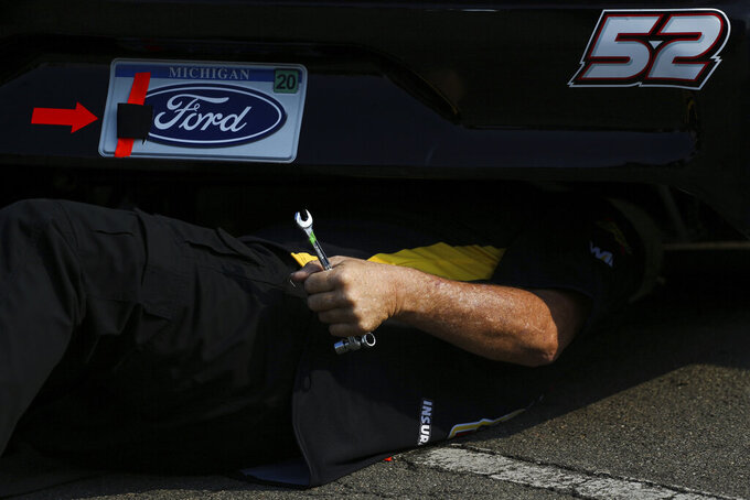 A member of Josh Bilicki's pit crew work on the car in the garage area before a NASCAR Cup series auto race in Watkins Glen, N.Y., on Sunday, Aug. 8, 2021. (AP Photo/Joshua Bessex)