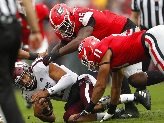 Texas A&M quarterback Kellen Mond (11) is sacked by Georgia defensive lineman Devonte Wyatt (95) and linebacker Jermaine Johnson (11) in the first half of an NCAA college football game Saturday, Nov. 23, 2019, in Athens, Ga. (AP Photo/John Bazemore)