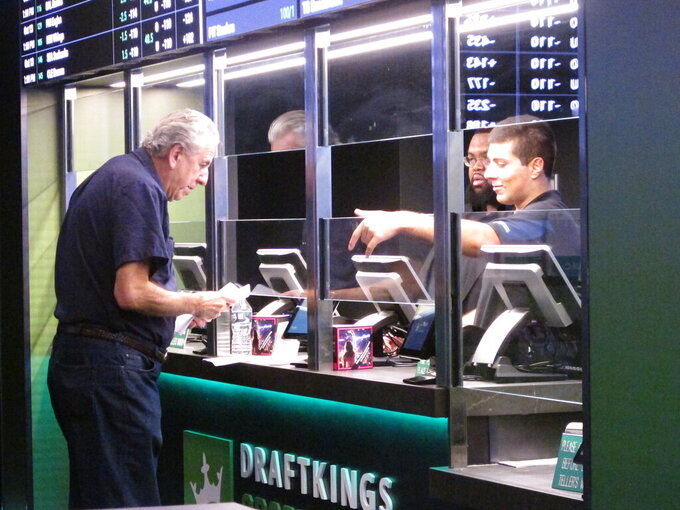 FILE - In this Oct. 8, 2019, file photo, a man makes a sports bet at Resorts casino in Atlantic City, N.J. Sports books say the blitz of advertising they launched in the run up to the 2021 Super Bowl, while costly, paid off in terms of attracting new customers to the fast-growing legal sports betting industry in the U.S. (AP Photo/Wayne Parry, File)