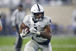In the rain, Penn State's Journey Brown rushes against Michigan State during the fourth quarter of an NCAA college football game, Saturday, Oct. 26, 2019, in East Lansing, Mich. (AP Photo/Al Goldis)