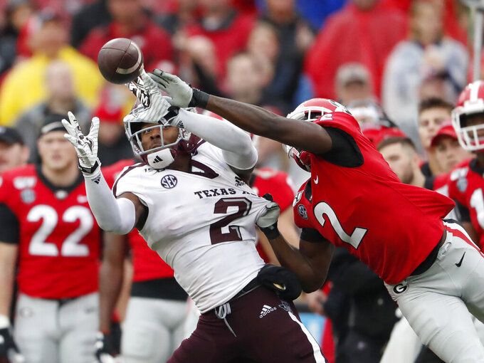 Texas A&M wide receiver Jhamon Ausbon (2) makes a catch as Georgia defensive back Richard LeCounte (2) defends in the first half of an NCAA college football game Saturday, Nov. 23, 2019, in Athens, Ga. (AP Photo/John Bazemore)