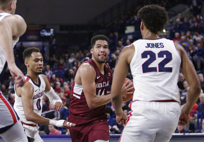 Santa Clara forward Keshawn Justice, center, drives to the basket while defended by Gonzaga forward Jeremy Jones (22) and Gonzaga guard Geno Crandall (0) during the second half of an NCAA college basketball game in Spokane, Wash., Saturday, Jan. 5, 2019. (AP Photo/Young Kwak)