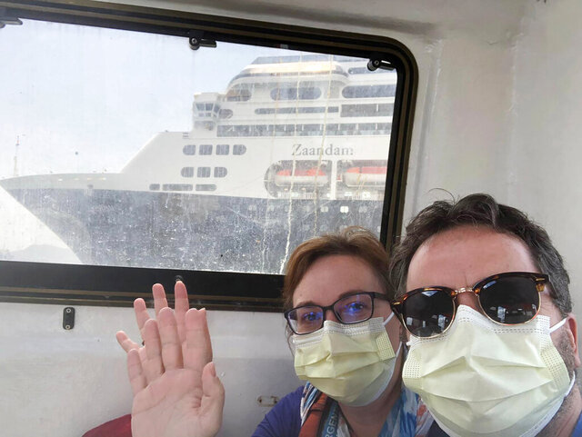 In this March 28, 2020 photo provided by Juan Huergo, Laura Gabaroni and her husband Juan Huergo take a selfie on board a tender after they were evacuated from the Zaandam, a Holland American cruise ship, near the Panama Canal. The Orlando- area couple was transferred to the Rotterdam, together with others who were deemed healthy. Four people have died on board the Zaandam and many others have are suffering from flu-like symptoms. (Juan Huergo via AP)