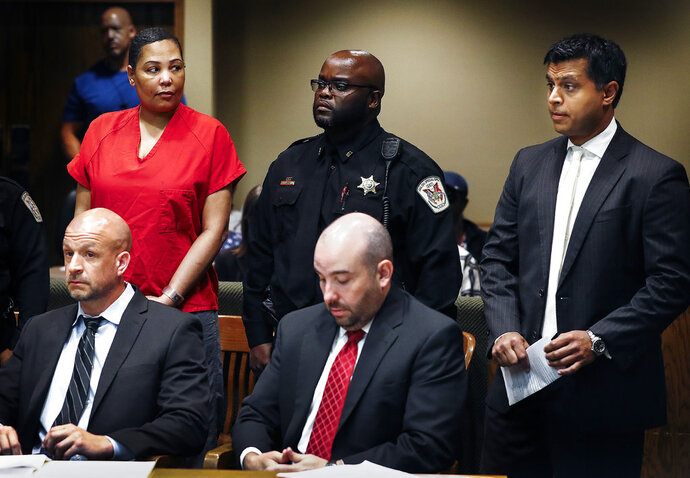 Sherra Wright, left, the ex-wife of slain former NBA player Lorenzen Wright, glances at her new court appointed attorneys Juni Ganguli, right, after her lawyers Steve Farese Jr. and Blake Ballin asked to be withdrawn from representing her during an appearance in Judge Lee Coffee's courtroom Wednesday, July 11, 2018 in Memphis. Shelby County Criminal Court Judge Lee Coffee granted a motion from Farese Jr. and Ballin for their removal from the case of Wright. She is charged with murder in the July 2010 slaying of Lorenzen Wright.  (Mark Weber/The Commercial Appeal via AP)
