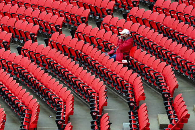 A fan waits in Arrowhead Stadium for the start of an NFL football game between the Kansas City Chiefs and the Houston Texans Thursday, Sept. 10, 2020, in Kansas City, Mo. About 16,000 fans are expected to attend the game. (AP Photo/Jeff Roberson)