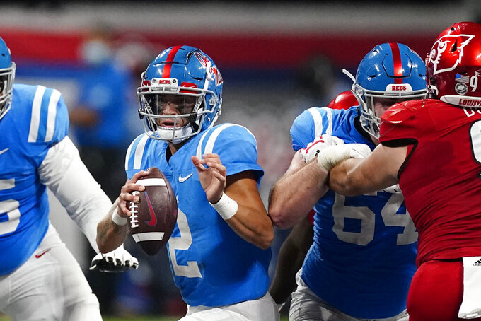 Mississippi quarterback Matt Corral (2) scrambles as Nick Broeker (64) blocks Louisville defensive lineman Derek Dorsey (91) during the second half of an NCAA college football game Monday, Sept. 6, 2021, in Atlanta. (AP Photo/John Bazemore)