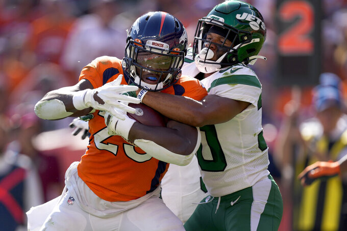 Denver Broncos running back Melvin Gordon (25) is tackled by New York Jets cornerback Michael Carter II during the first half of an NFL football game, Sunday, Sept. 26, 2021, in Denver. (AP Photo/David Zalubowski)