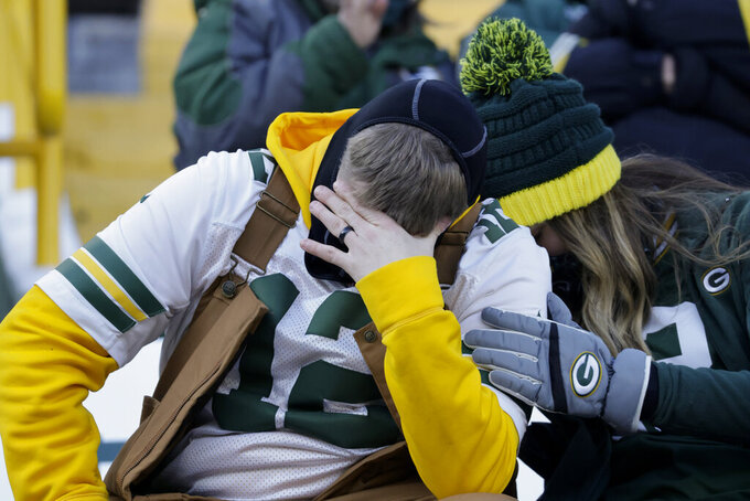 Packer fans react during the first half of the NFC championship NFL football game between the Tampa Bay Buccaneers and Green Bay Packers in Green Bay, Wis., Sunday, Jan. 24, 2021. (AP Photo/Jeffrey Phelps)