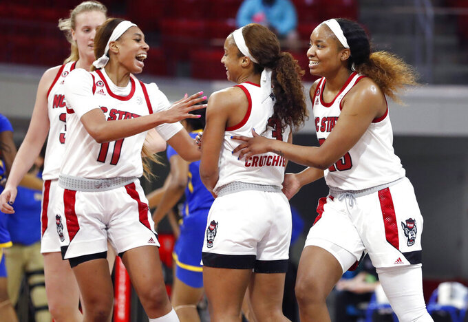 North Carolina State's Jakia Brown-Turner (11) and Kayla Jones, right, celebrate with Kai Crutchfield (3) during the second half against Pittsburgh in an NCAA college basketball game in Raleigh, N.C., Thursday, Feb. 25, 2021. (Ethan Hyman/The News & Observer via AP, Pool)