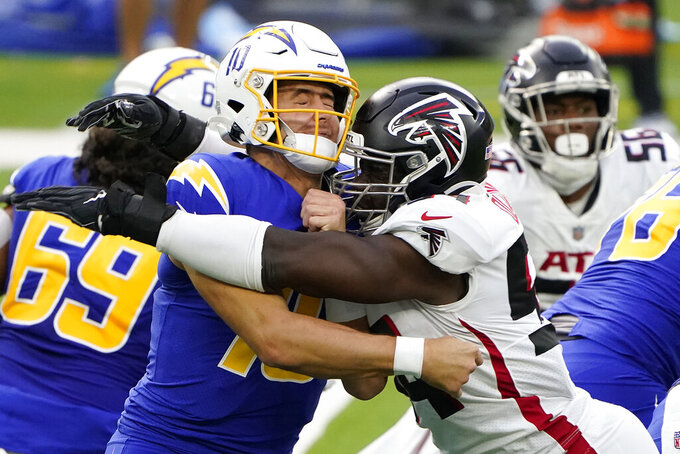 Los Angeles Chargers quarterback Justin Herbert, left, is hit by Atlanta Falcons linebacker Foyesade Oluokun as he throws during the first half of an NFL football game Sunday, Dec. 13, 2020, in Inglewood, Calif. (AP Photo/Jae C. Hong)