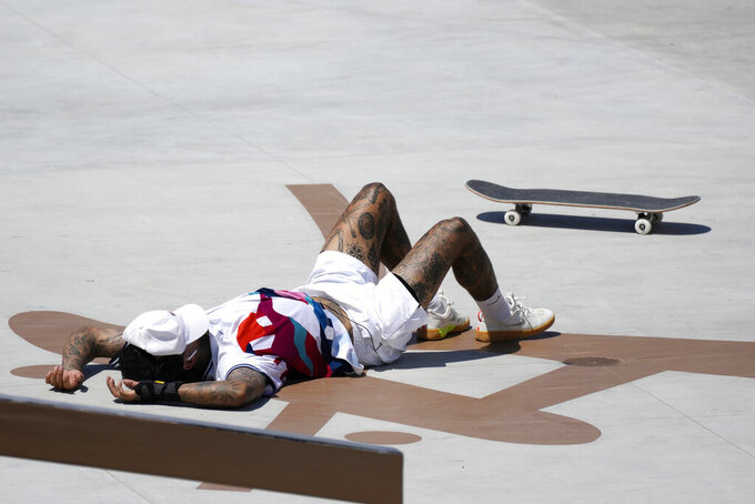 Nyjah Huston of the United States falls during competition in the men's street skateboarding at the 2020 Summer Olympics, Sunday, July 25, 2021, in Tokyo, Japan. (AP Photo/Ben Curtis)