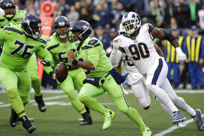 Seattle Seahawks quarterback Russell Wilson, center, scrambles away from Los Angeles Rams defensive end Michael Brockers (90) during the first half of an NFL football game Thursday, Oct. 3, 2019, in Seattle. (AP Photo/Elaine Thompson)