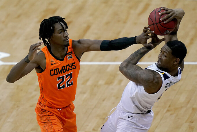 Oklahoma State's Kalib Boone (22) tries to steal the ball from West Virginia's Gabe Osabuohien during the second half of an NCAA college basketball game in the second round of the Big 12 men's tournament in Kansas City, Mo., Thursday, March 11, 2021. Oklahoma State won 72-69. (AP Photo/Charlie Riedel)