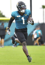 Jacksonville Jaguars' Travis Etienne Jr. runs with the ball after making a catch during an NFL football training camp in Jacksonville, Fla., Tuesday, Aug. 3, 2021. (Bob Self/The Florida Times-Union via AP)