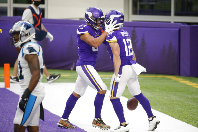 Minnesota Vikings wide receiver Chad Beebe (12) celebrates with teammate Bisi Johnson, left, after catching a 10-yard touchdown pass during the second half of an NFL football game against the Carolina Panthers, Sunday, Nov. 29, 2020, in Minneapolis. The Vikings won 28-27. (AP Photo/Bruce Kluckhohn)