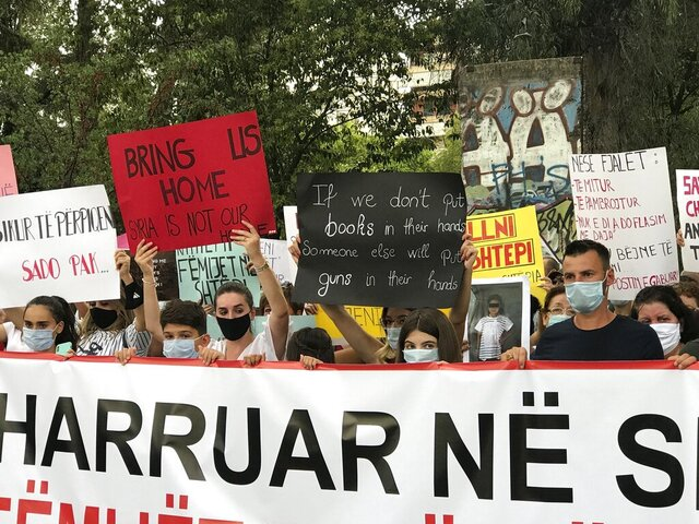 Protesters hold up placards during a rally in front of the government building in Tirana, Albania, Monday, Sept. 14, 2020. Scores of family members of 52 children who have remained in Syria after their parents joined Islamic terror groups gathered in front of the main government building shouting for help, calling on the government to keep the pledge to bring their children back. (AP Photo/Llazar Semini)