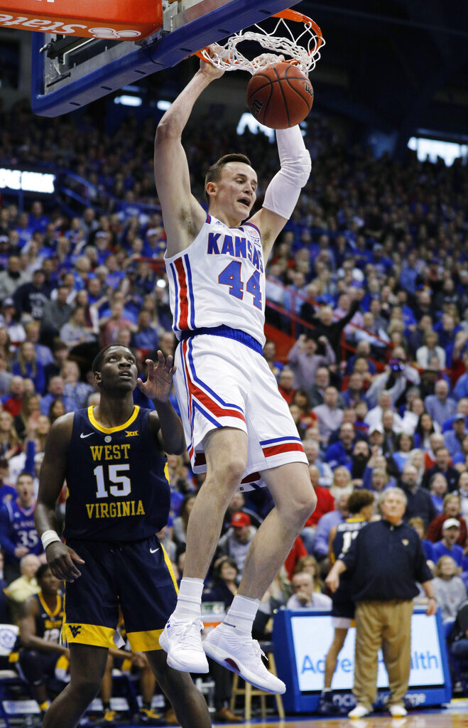 Kansas forward Mitch Lightfoot (44) dunks the ball as West Virginia forward Lamont West (15) watches during the first half of an NCAA college basketball game, Saturday, Feb. 16, 2019, in Lawrence, Kan. (AP Photo/Colin E. Braley)