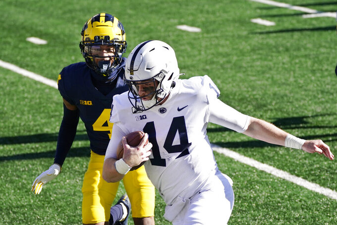Penn State quarterback Sean Clifford, chased by Michigan defensive back Vincent Gray (4) runs for a 28-yard touchdown during the first half of an NCAA college football game, Saturday, Nov. 28, 2020, in Ann Arbor, Mich. (AP Photo/Carlos Osorio)