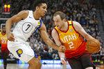 Indiana Pacers guard Malcolm Brogdon (7) guards Utah Jazz forward Joe Ingles (2) in the second half of an NBA basketball game Monday, Jan. 20, 2020, in Salt Lake City. (AP Photo/Rick Bowmer)