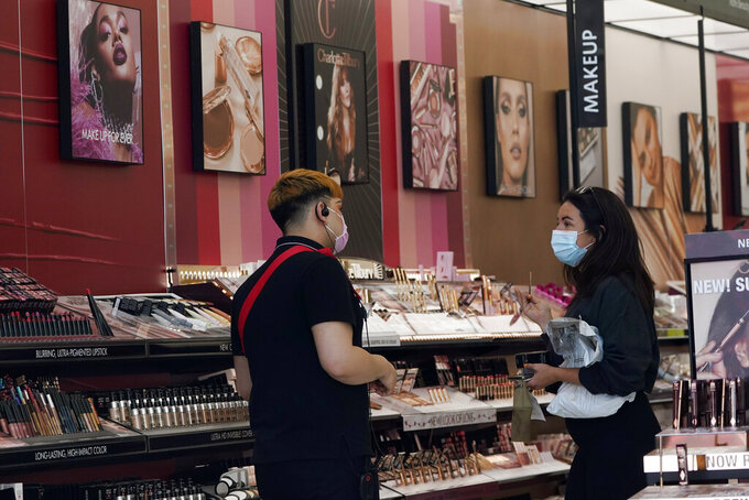 A worker, at left, tends to a customer at a cosmetics shop amid the COVID-19 pandemic Thursday, May 20, 2021, in Los Angeles. (AP Photo/Marcio Jose Sanchez)