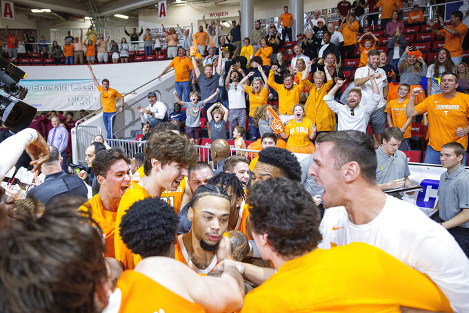 Tennessee players swarm guard Lamonte Turner, center, after hitting the game-winning shot at the buzzer against Virginia Commonwealth in an NCAA college basketball game in the Emerald Coast Classic in Niceville, Fla., Saturday, Nov. 30, 2019. Tennessee won 72-69. (AP Photo/Mark Wallheiser)