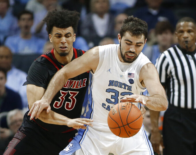 Louisville's Jordan Nwora (33) tries to steal the ball from North Carolina's Luke Maye (32) during the first half of an NCAA college basketball game in the Atlantic Coast Conference tournament in Charlotte, N.C., Thursday, March 14, 2019. (AP Photo/Nell Redmond)