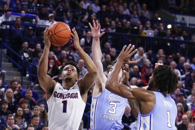 Gonzaga guard Admon Gilder, left, shoots against North Carolina guard Andrew Platek, center, and guard Leaky Black during the second half of an NCAA college basketball game in Spokane, Wash., Wednesday, Dec. 18, 2019. Gonzaga won 94-81. (AP Photo/Young Kwak)