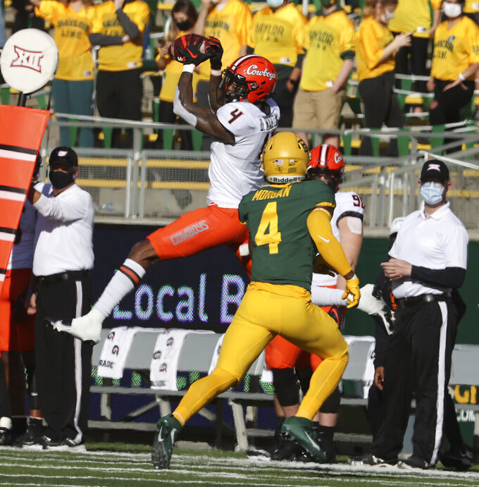 Oklahoma State wide receiver Tay Martin, left, pulls down a pass over Baylor safety Christian Morgan, right, in the first half of an NCAA college football game, Saturday, Dec. 12, 2020, in Waco, Texas. (Rod Aydelotte/Waco Tribune-Herald via AP)