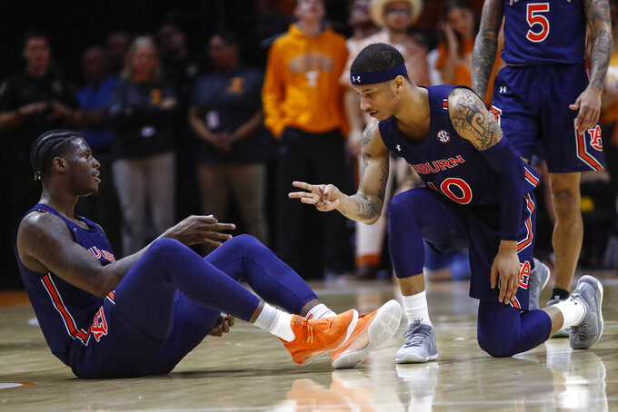 Auburn guard Samir Doughty (10) and forward Danjel Purifoy (3) react to a 3-point shot during an NCAA college basketball game against Tennessee, Saturday, March 7, 2020, in Knoxville, Tenn. Doughty made 8 of 13 3-pointers and finished with 32 points as No. 17 Auburn beat Tennessee 85-63 to snap a two-game skid in the regular-season finale. (AP Photo/Wade Payne)