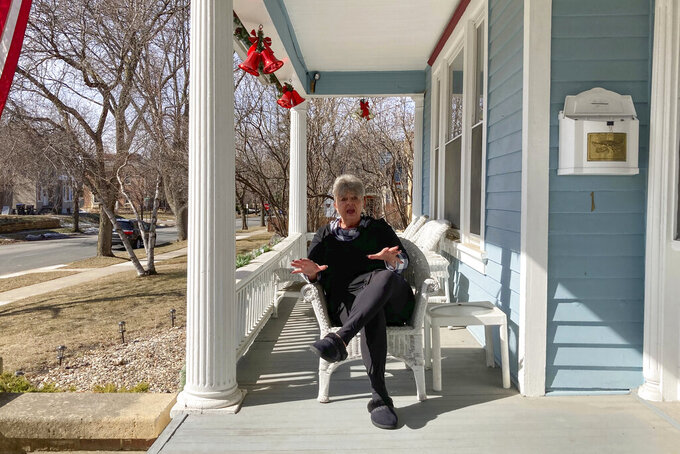 In this March 8, 2021, photo, sitting on her porch, in Mankato, Minn., Jaci Lageson explains why she supports compromises President Joe Biden made with conservative Democrats to win passage of the $1.9 trillion COVID-19 relief bill. Biden carried Blue Earth County, Minnesota, where Republican Donald Trump won in part due to heavy support for the Democrat in Lageson's precinct in this small, Midwestern city. (AP Photo/Tom Beaumont)