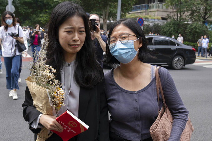 Zhou Xiaoxuan, left, a former intern at China's state broadcaster CCTV, reacts as she arrives to attend a court session at a courthouse in Beijing, Tuesday, Sept. 14, 2021. Zhou became the face of the country's MeToo movement after going public with accusations against a prominent CCTV host in 2018. Since then, even as the movement was shut down by authorities, Zhou has continued to speak out. (AP Photo/Mark Schiefelbein)