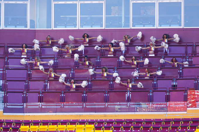 Members of the Washington Football Team cheerleading squad performing in an empty deck seating area of FedEx Field during the first half of an NFL football game between the New York Giants and Washington Football Team, Sunday, Nov. 8, 2020, in Landover, Md. (AP Photo/Al Drago)