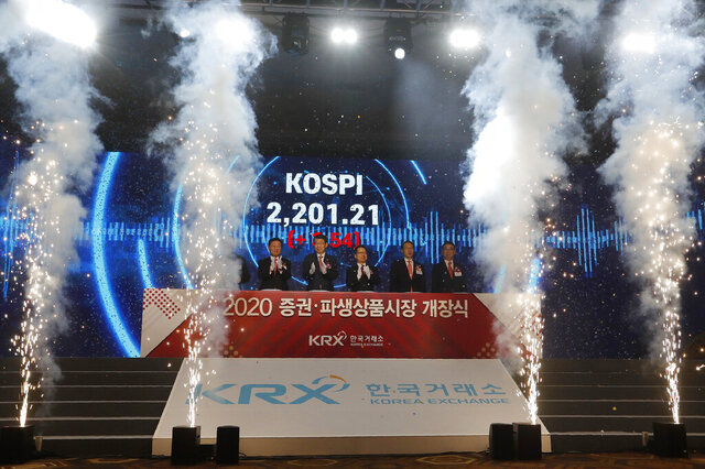 Jung Ji-won, third from left, chief executive of the Korea Exchange, and Financial Services Commission Chairman Eun Sung-soo, fourth from left, applaud with other participants during the opening of this year's trading in Seoul, South Korea, Thursday, Jan. 2, 2020. The sign read: