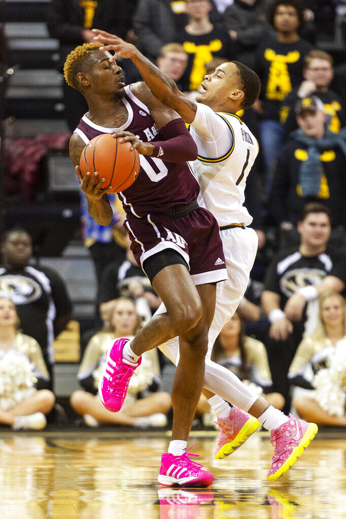 Texas A&M's Jay Jay Chandler, left, is fouled by Missouri's Xavier Pinson, right, during the second half of an NCAA college basketball game Tuesday, Jan. 21, 2020, in Columbia, Mo. Texas A&M won the game 66-64. (AP Photo/L.G. Patterson)