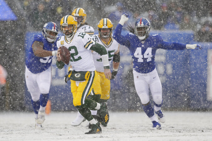 Green Bay Packers quarterback Aaron Rodgers, front, runs with the ball during the first half of an NFL football game against the New York Giants, Sunday, Dec. 1, 2019, in East Rutherford, N.J. (AP Photo/Adam Hunger)