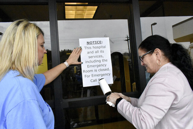 In this March 19, 2020, photo, Carol Talkington helps Terri Bonasso tape a notice on the emergency room door following a vigil at the closing of the Fairmont Regional Medical Center in Fairmont, W.Va. The coronavirus pandemic couldn't come at a worse time for communities trying to cope after a wave of hospital shutdowns across the rural United States. (Tammy Shriver/Times-West Virginian via AP)
