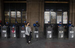 Wearing masks to curb the spread of the new coronavirus, police guard the city government building during a protest in Mexico City, Wednesday, Aug. 26, 2020. (AP Photo/Marco Ugarte)