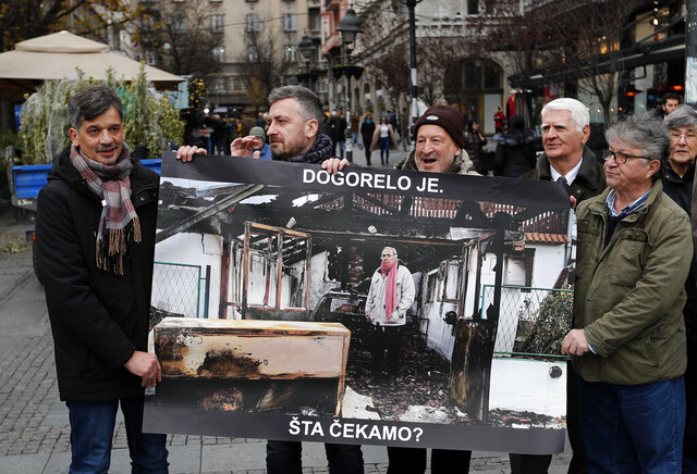 Members of the Independent Journalists' Association hold a poster shows a journalist Milan Jovanovic in his burned house that reads: