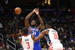 Philadelphia 76ers center Joel Embiid (21) loses the ball after he was fouled by Washington Wizards guard Bradley Beal (3) during the first half of an NBA basketball game, Thursday, Dec. 5, 2019, in Washington. Also seen is Wizards center Ian Mahinmi (28). (AP Photo/Nick Wass)
