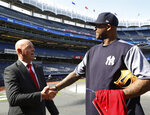 In this Wednesday, May 8, 2019 photo, former Liverpool goalkeeper Bruce Grobbelaar, left, speaks to New York Yankees pitcher CC Sabathia as the pair met on the field at Yankee Stadium in New York. When Grobbelaar celebrated at Anfield on April 28, 1990, he never thought it would be Liverpool's last league title in three decades. (AP Photo/Kathy Willens)