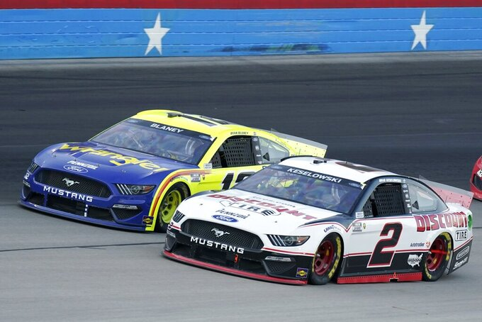 Brad Keselowski (2) and Ryan Blaney, rear, come out of turn four competing for position during the NASCAR Cup Series All-Star auto race at Texas Motor Speedway in Fort Worth, Texas, Sunday, June 13, 2021. (AP Photo/Tony Gutierrez)