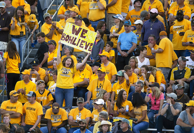 A Wyoming fan showing her support for head coach Craig Bohl celebrates after a touchdown against Missouri in the second quarter of an NCAA college football game, Saturday, Aug. 31, 2019, in Laramie, Wyo. (AP Photo/Michael Smith)