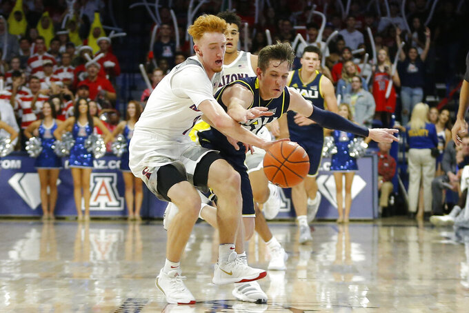 Arizona guard Nico Mannion, left, and Northern Arizona guard Luke Avdalovic vie for a loose ball during the second half of an NCAA college basketball game, Wednesday, Nov. 6, 2019, in Tucson, Ariz. (AP Photo/Rick Scuteri)