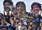 Fans of the Gimnasia y Esgrima La Plata soccer team hold up photos of their team's new head coach, Diego Maradona, at a local tournament soccer match against Racing Club at Juan Carmelo Zerillo stadium in La Plata, Argentina, Sunday, Sept. 15, 2019. (AP Photo/Gustavo Garello)