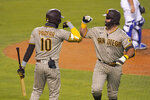 San Diego Padres' Austin Hedges, right, is congratulated by Jurickson Profar after hitting a solo home run during the fifth inning of a baseball game against the Los Angeles Dodgers Monday, Aug. 10, 2020, in Los Angeles. (AP Photo/Mark J. Terrill)