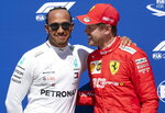 Mercedes driver Lewis Hamilton, left, of Great Britain congratulates Ferrari driver Sebastian Vettel of Germany for taking the pole position during qualifying for the Formula One Canadian Grand Prix auto race in Montreal, Saturday, June 8, 2019. (Paul Chiasson/The Canadian Press via AP)
