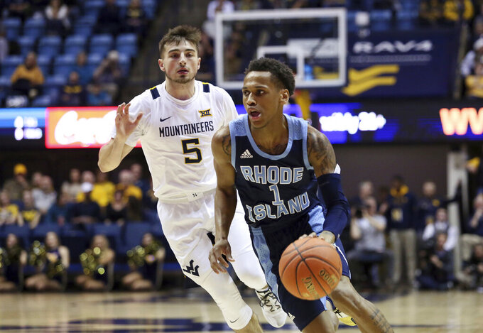 Rhode Island guard Fatts Russell (1) drives it up court as he is defended by West Virginia guard Jordan McCabe (5) during the first half of an NCAA college basketball game Sunday, Dec. 1, 2019, in Morgantown, W.Va. (AP Photo/Kathleen Batten)